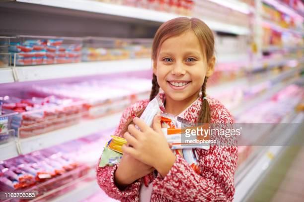 charmante glückliche mädchen mit süßen bars im geschäft - kuchen und süßwaren stock-fotos und bilder