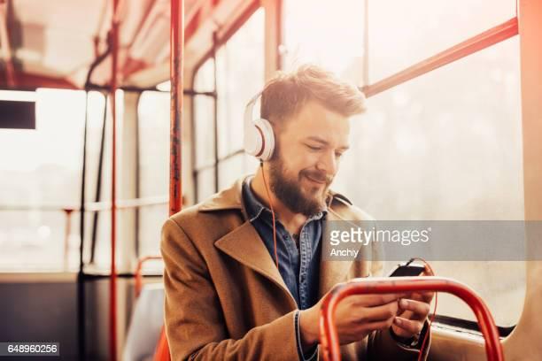 Hombre encantador escuchar música con auriculares en un autobús público