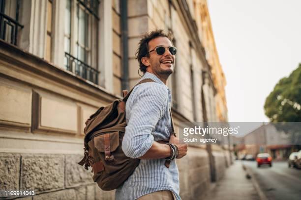 charming man with backpack in city - solo un uomo foto e immagini stock