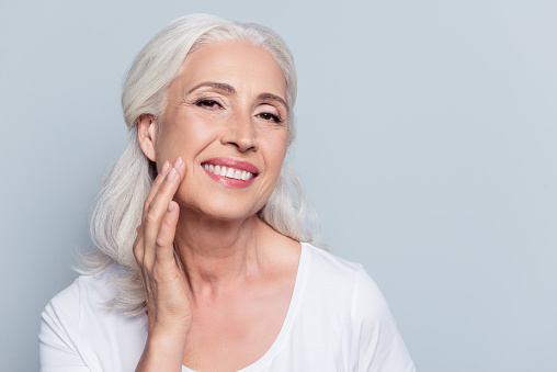 Charming, pretty, old woman touching her perfect soft face skin with fingers, smiling at camera over gray background, using day, night face cream, cosmetology procedures 924170478
