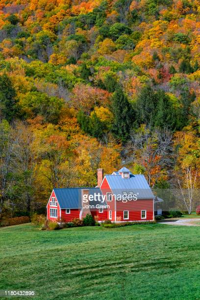 Charming red house flanked by autumn foliage