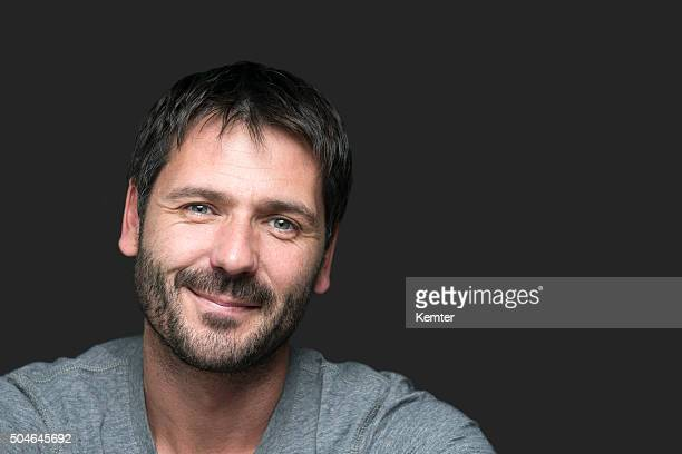 charming smiling man portrait isolated on gray - mid adult stock pictures, royalty-free photos & images