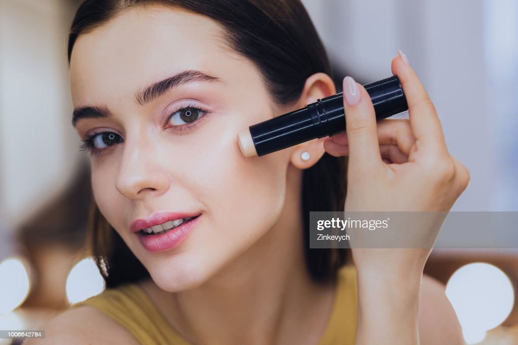 Charming woman using concealer stick while putting makeup on : Stock Photo