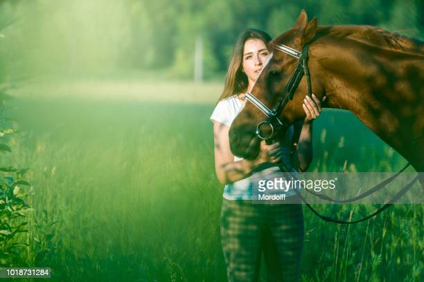 charming woman with horse among green plants - dressage horse russia stock photos and pictures