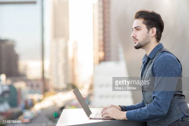 charming young man working on his laptop in the city - 男性用ベスト ストックフォトと画像