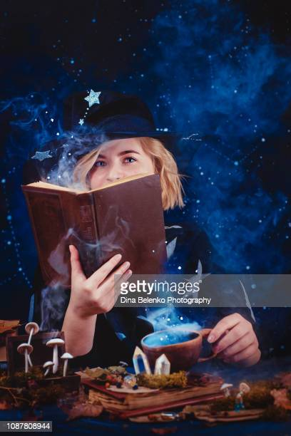 charming young witch with a book of spells and magical potions. magical workplace with candles, mysterious smoke, crystals and mushrooms. dark background with stars and copy space - potion stock photos and pictures