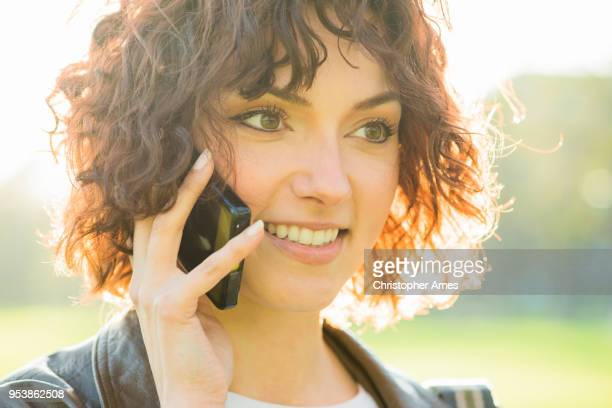 charming young woman on the phone - permed hair stock photos and pictures