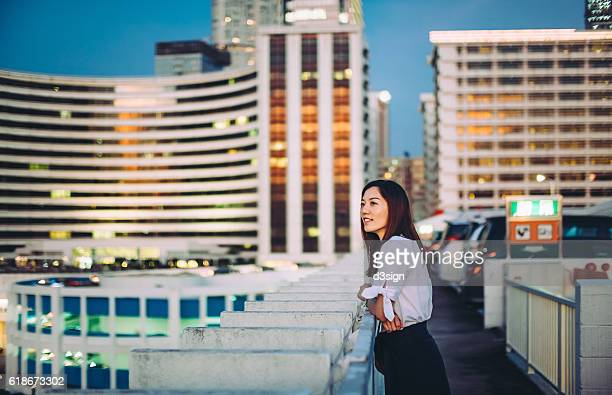Charming young woman with smile leaning on rooftop terrace overlooking the beautiful skyline of Hong Kong