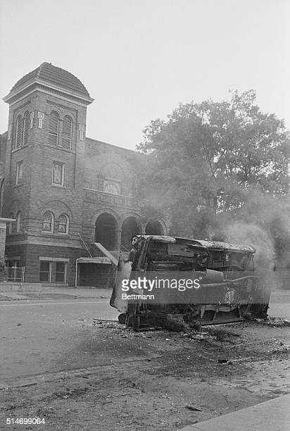 A charred automobile sits outside of the 16th Street Baptist Church where followers of Reverend Martin Luther King Jr regularly meet