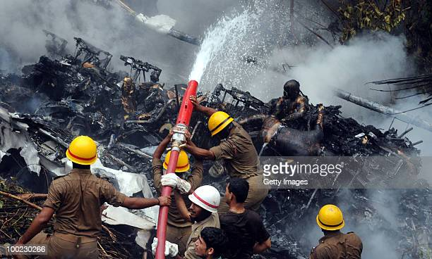 Charred bodies of passengers remain in the wreakage of the aircraft crash as firemen hose it down on May 22 2010 in Mangalore An Air India Express...