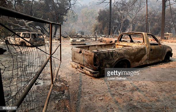 Charred cars sit near a burned down home September 2 2009 at Vogel Flats near Tujunga California Fire officials said that the deadly 140000 acre...