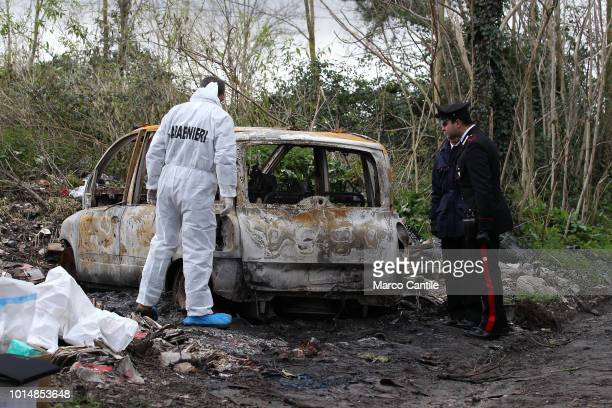 Charred corpse in a car burned on a country path. The scientific police and the Carabinieri are close to the car.