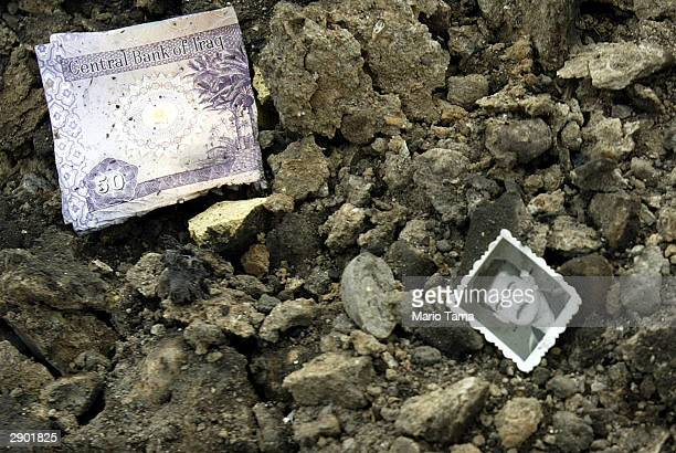 A charred Iraqi Dinar and a photograph lie in rubble at the scene of a roadside bombing January 26 2004 in Baghdad Iraq The bomb destroyed a bus...