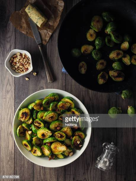 charred sprouts with spicy herb butter and fine chopped hazelnuts - nut food stock photos and pictures