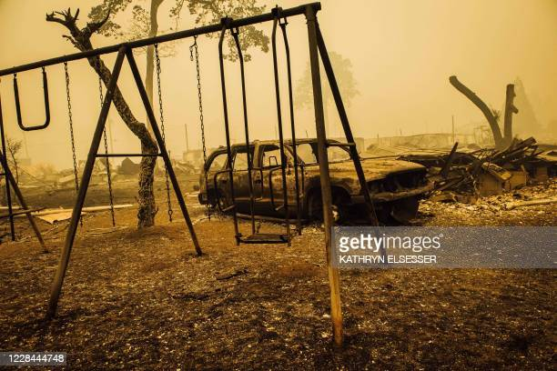Charred swing set and car are seen after the passage of the Santiam Fire in Gates, Oregon, on September 10, 2020. - California firefighters battled...