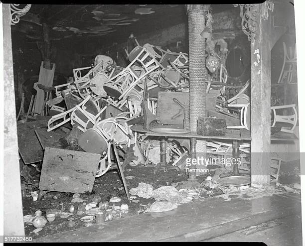 Charred tables and chairs broken wine glasses and other debris clutter a section of Boston's destroyed Cocoanut Grove Night Club Fire swept through...