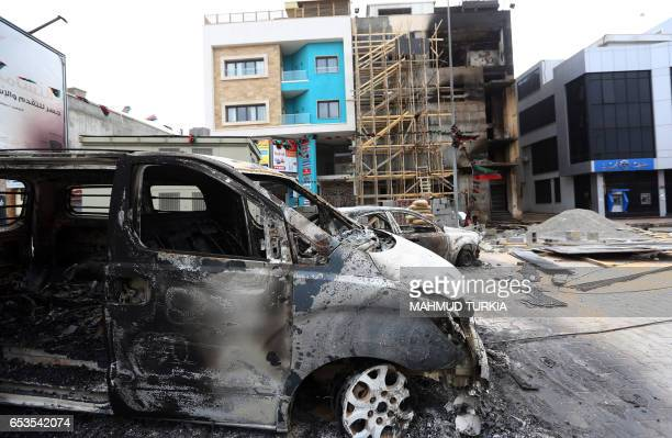 Charred vehicles are pictured outside the quarters of the Libyan AlNabaa TV channel in the capital Tripoli following exchanges of rocket and...