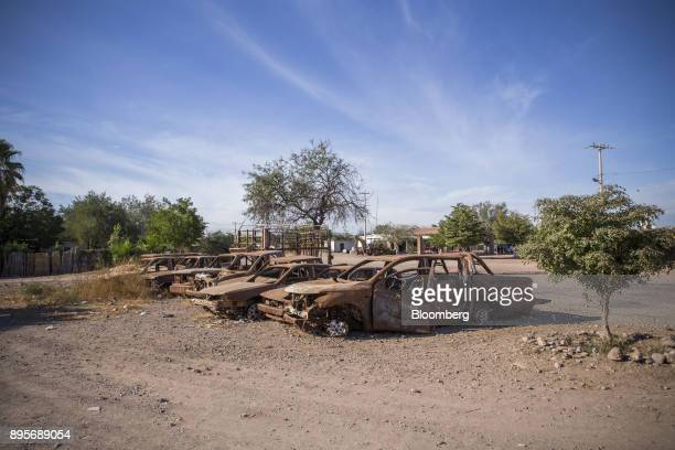 Charred vehicles burned during a clash over defendants and opponents of the Sempra Energy pipeline sit outside of the community center in the village...