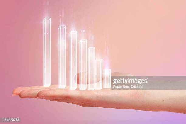Chart resting on hand with pink studio background