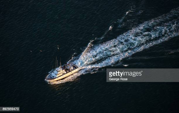 A charter fishing boat heads back to the harbor as viewed in this sunset aerial photo taken on December 4 over Santa Barbara California Because of...