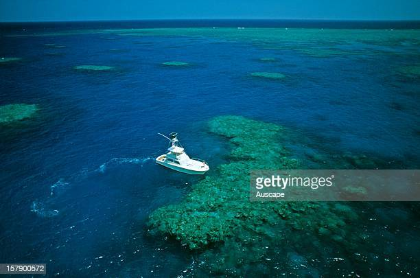 Charter vessel 'Sea Venture' among coral bommies from the air Great Barrier Reef Queensland Australia