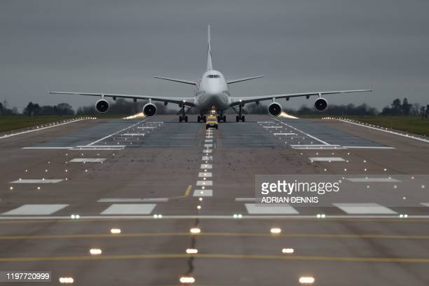 A chartered passenger jet carrying evacuated citizens from China taxis on the runway after landing at the Royal Air Force station RAF Brize Norton in...