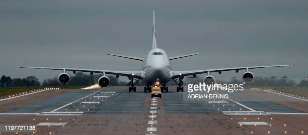 TOPSHOT A chartered passenger jet carrying evacuated citizens from China taxis on the runway after landing at the Royal Air Force station RAF Brize...