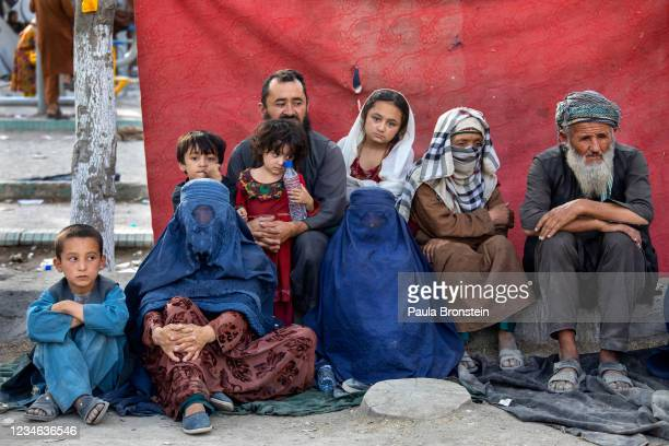 Charyar from the Balkh province sits alongside his family at a makeshift IDP camp in Share-e-Naw park to various mosques and schools on August 12,...