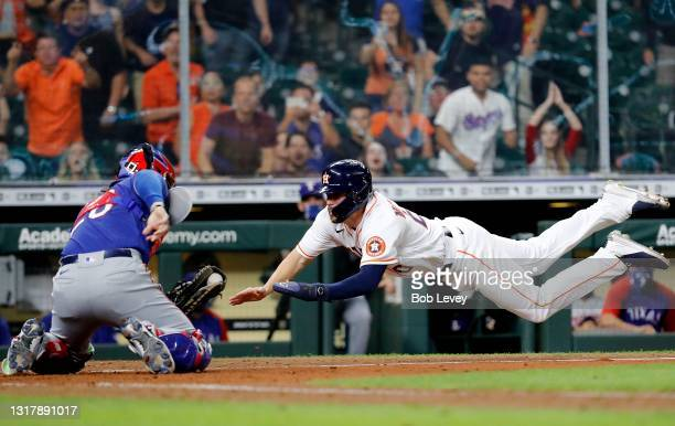 Chas McCormick of the Houston Astros is tagged out by Jose Trevino of the Texas Rangers while attempting to score on a fly ball in the tenth inning...