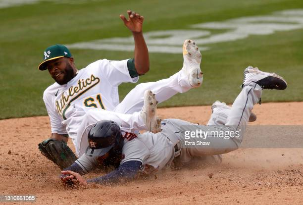 Chas McCormick of the Houston Astros slides safely under pitcher Reymin Guduan of the Oakland Athletics after Guduan threw a wild pitch and McCormick...