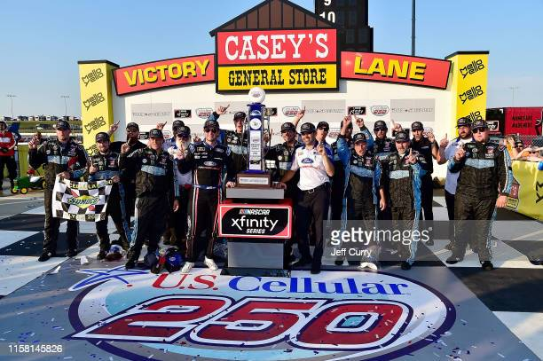 Chase Briscoe, driver of the Ford Performance Ford, and his team pose for a photo after winning the NASCAR Xfinity Series U.S. Cellular 250 at Iowa...