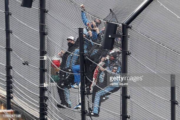 Chase Briscoe, driver of the Highpoint.com Ford, and crew climb the fence after winning the the NASCAR Xfinity Series Pennzoil 150 at the Brickyard...