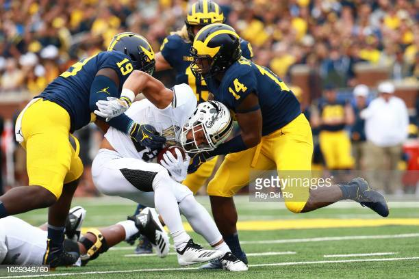 Chase Brown of the Western Michigan Broncos runs the ball and is tackled by Kyle Grady and Kwity Paye of the Michigan Wolverines at Michigan Stadium...