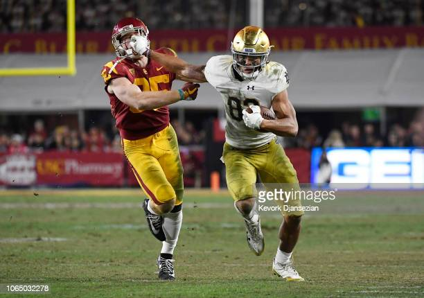 Chase Claypool of the Notre Dame Fighting Irish grabs the helmet of Cameron Smith of the USC Trojans as he runs after a catch during the second half...