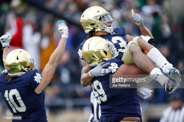 Chase Claypool of the Notre Dame Fighting Irish is lifted up by teammate Aaron Banks after a six-yard touchdown reception against the Boston College...