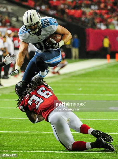 Chase Coffman of the Tennessee Titans leaps over Kemal Ishmael of the Atlanta Falcons in the second half of a preseason game at the Georgia Dome on...