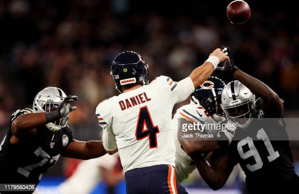 Chase Daniel of the Chicago Bears passes the ball while under pressure by Benson Mayowa of the Oakland Raiders and Maurice Hurst of the Oakland...