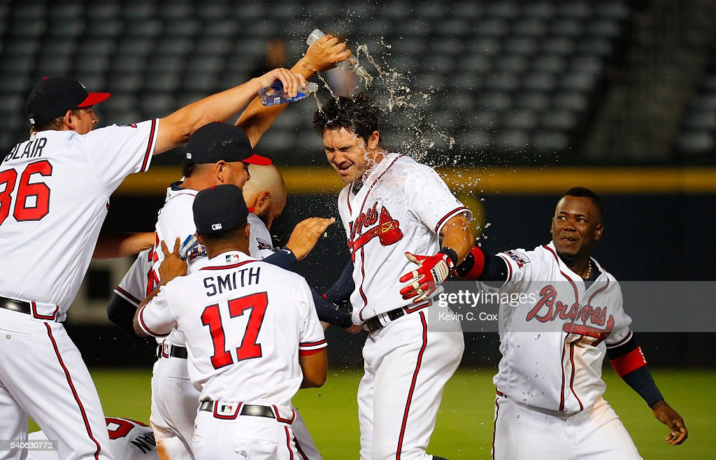 Chase d'Arnaud #23 celebrates with teammates after hitting a walk-off single to give the Braves a 9-8 win over the Cincinnati Reds in the 13th inning at Turner Field on June 15, 2016 in Atlanta, Georgia.