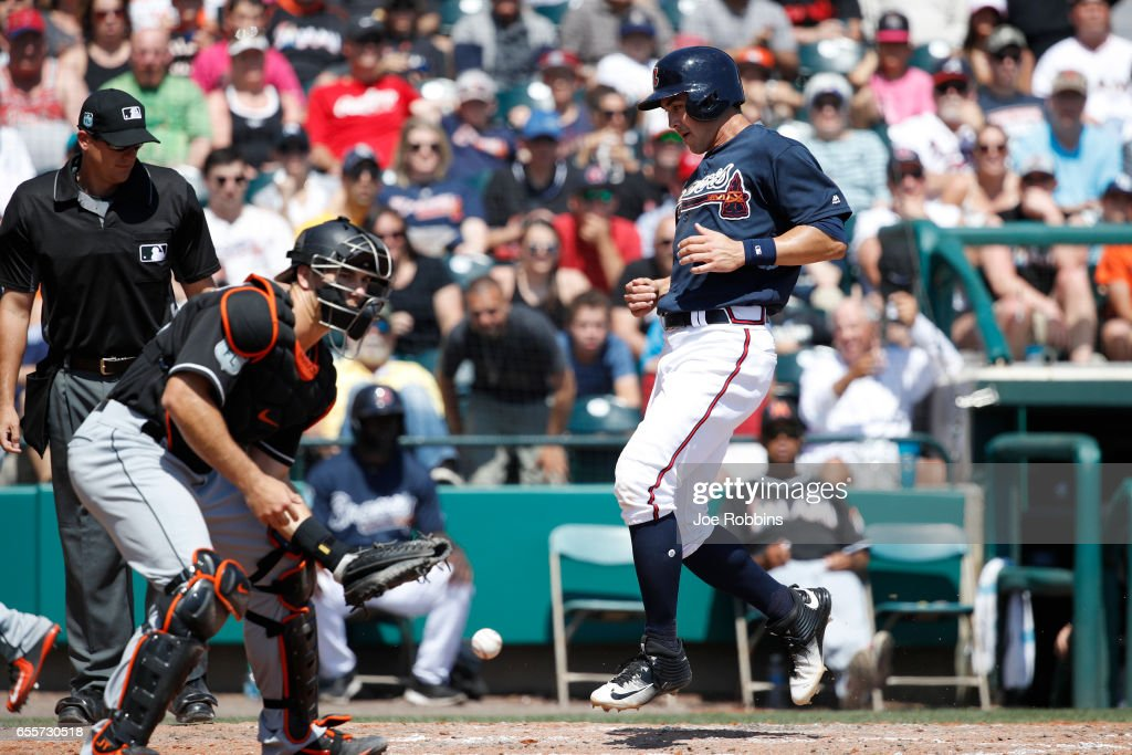 Chase d'Arnaud #23 of the Atlanta Braves scores after a single by Brandon Phillips in the fifth inning of a Grapefruit League spring training game against the Miami Marlins at Champion Stadium on March 20, 2017 in Lake Buena Vista, Florida. The Marlins defeated the Braves 9-3.