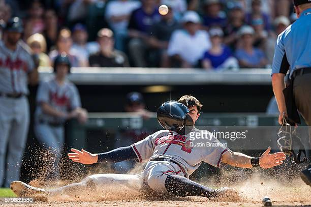 Chase d'Arnaud of the Atlanta Braves slides into home plate to score in the seventh inning of a game at Coors Field on July 24 2016 in Denver Colorado