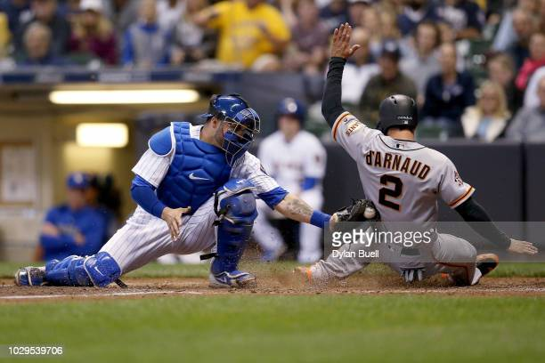 Chase d'Arnaud of the San Francisco Giants slides into home plate to score a run past Manny Pina of the Milwaukee Brewers in the sixth inning at...