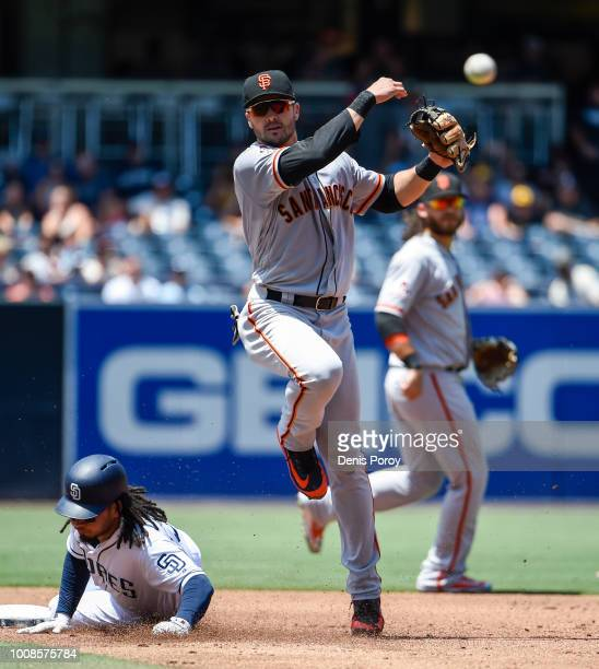 Chase d'Arnaud of the San Francisco Giants throws over Freddy Galvis of the San Diego Padres as he turns a double play during the second inning of a...