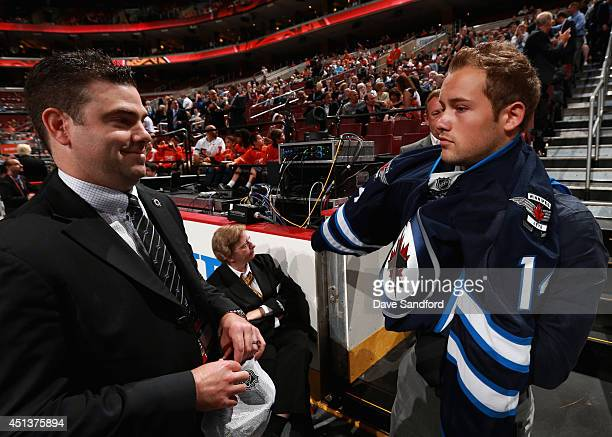 Chase De Leo puts on his jersey after being selected 99th overall by the Winnipeg Jets during the 2014 NHL Entry Draft at Wells Fargo Center on June...