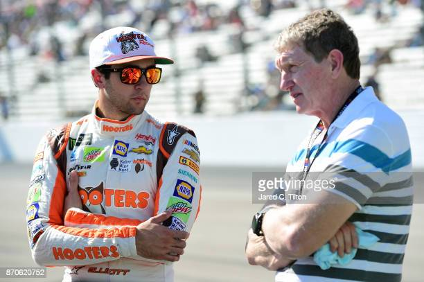 Chase Elliott driver of the Hooters Chevrolet stands on the grid with his father and NASCAR Hall of Famer Bill Elliott prior to the Monster Energy...