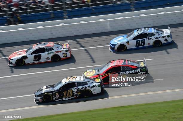 Chase Elliott driver of the Mountain Dew/Little Caesar's Chevrolet and Aric Almirola driver of the Smithfield Ford lead Martin Truex Jr driver of the...
