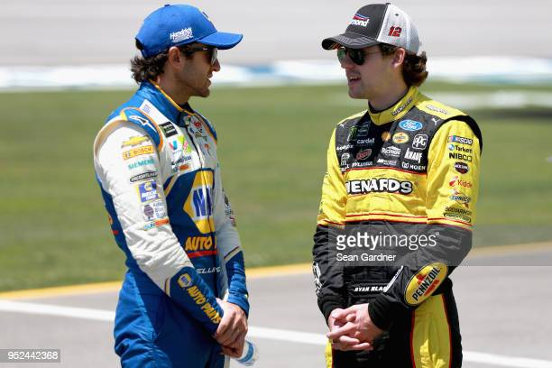 Chase Elliott driver of the NAPA Auto Parts Chevrolet talks to Ryan Blaney driver of the Menards/Richmond Ford on the grid during qualifying for the...