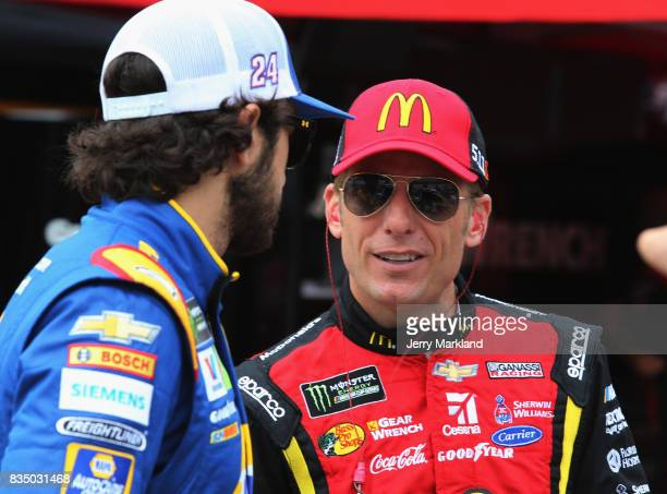 Chase Elliott driver of the NAPA Chevrolet talks to Jamie McMurray driver of the McDonalds/Cessna Chevrolet during practice for the Bass Pro Shops...