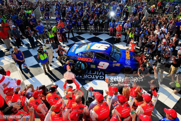 Chase Elliott driver of the SunEanergy1 Chevrolet and his team celebrate in Victory Lane after winning the Monster Energy NASCAR Cup Series GoBowling...