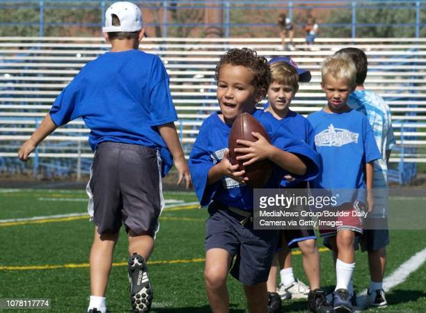 Chase Elliott takes a handoff from a fellow participant during the Broomfield youth football camp held at Elizabeth Kennedy Stadium on Wednesday