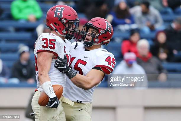 Chase Guillory and Luke Hutton of the Harvard Crimson react during a game against the Yale Bulldogs at the Yale Bowl on November 18 2017 in New Haven...